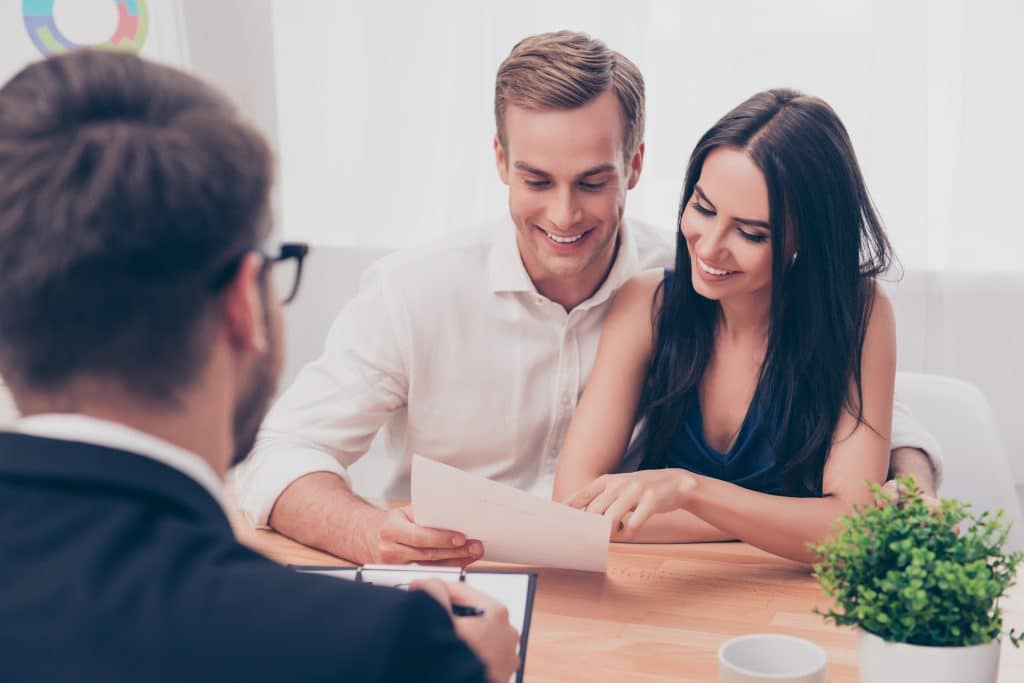 Successful sdvisor giving consultation to family couple about buy