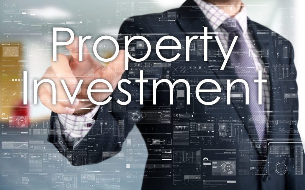 Man in a business suit in front of a glass board with Property Investment written on it in white