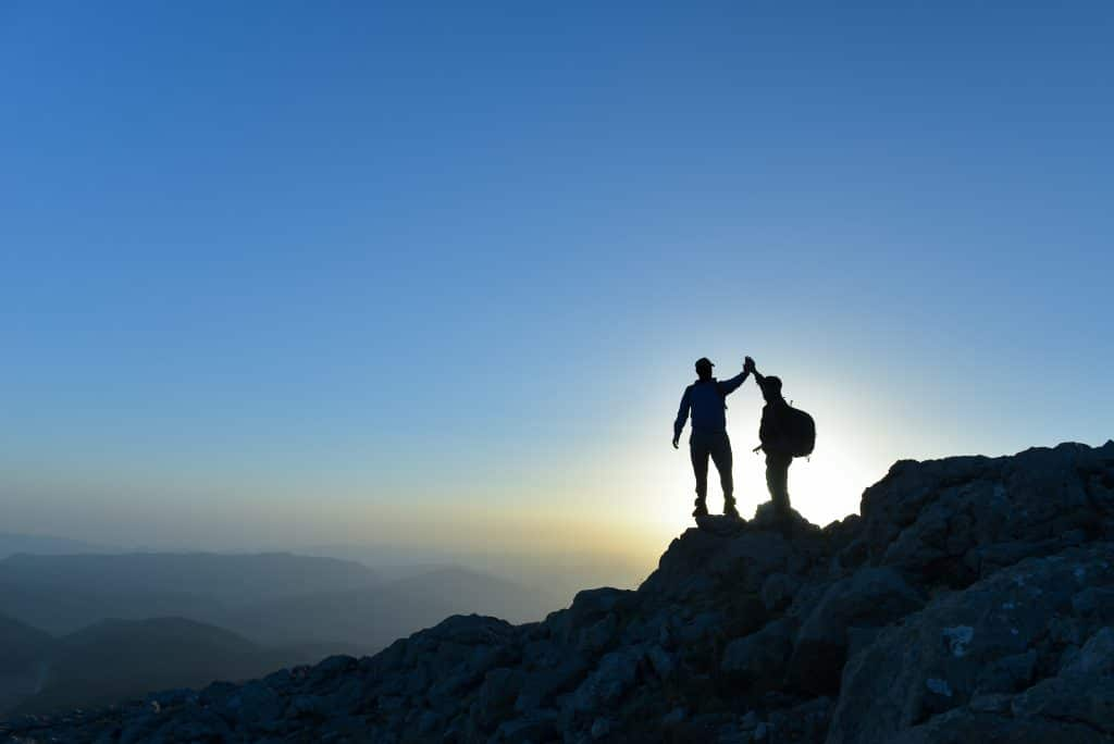 two people reaching goals and giving a high-five at the top