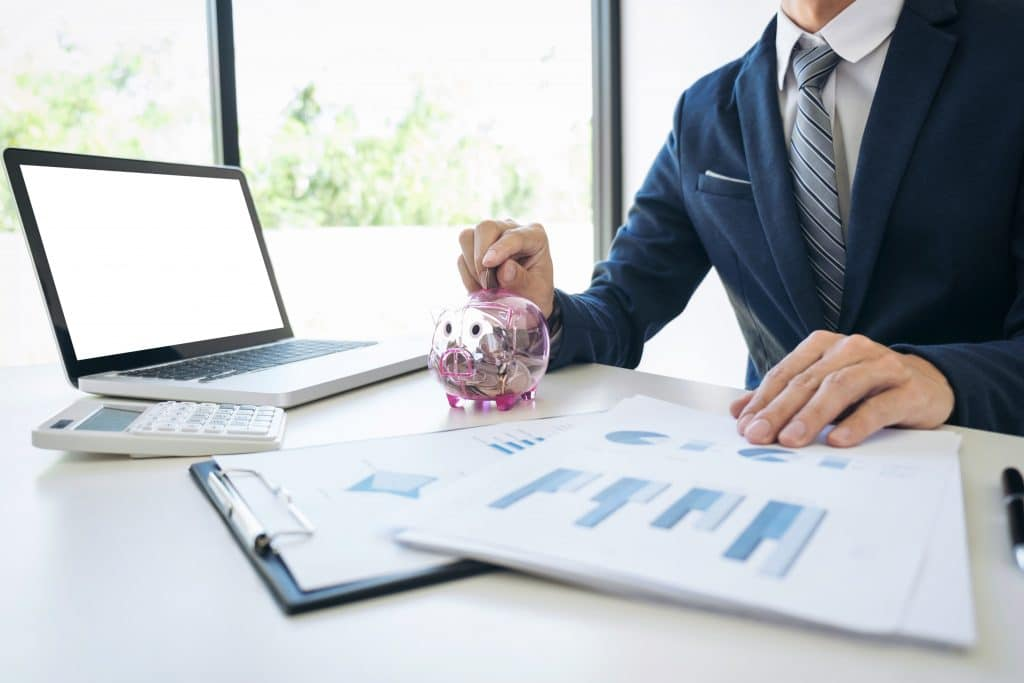 Businessman putting coins into piggy bank and using calculator to analyze tax savings with document graph data, financials
