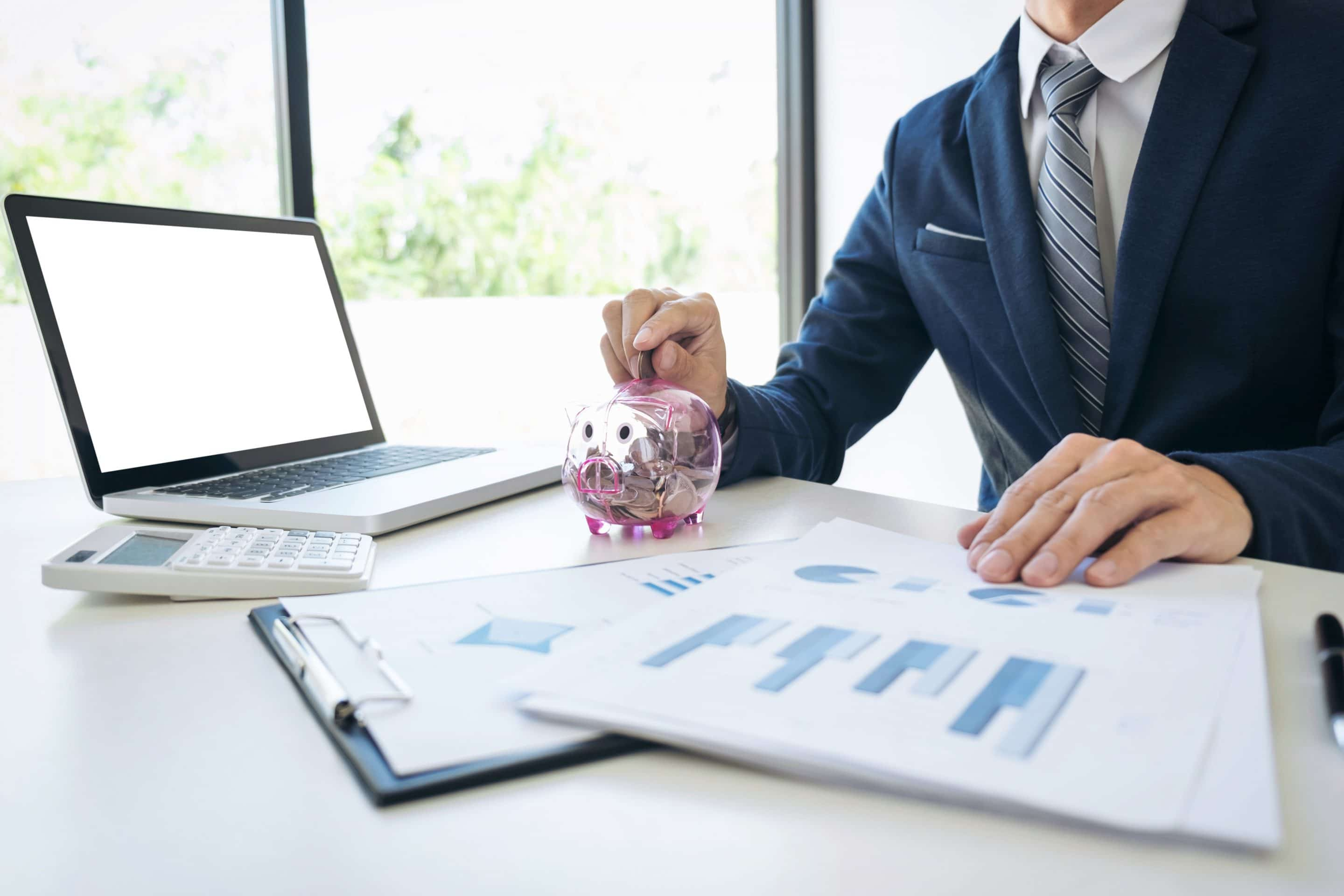 Businessman putting coins into piggy bank and using calculator to analysis business investment with many document graph data, financial concept