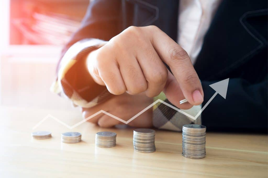 Woman putting coins on stack with holding money, Concept business, finance, money saving and investment