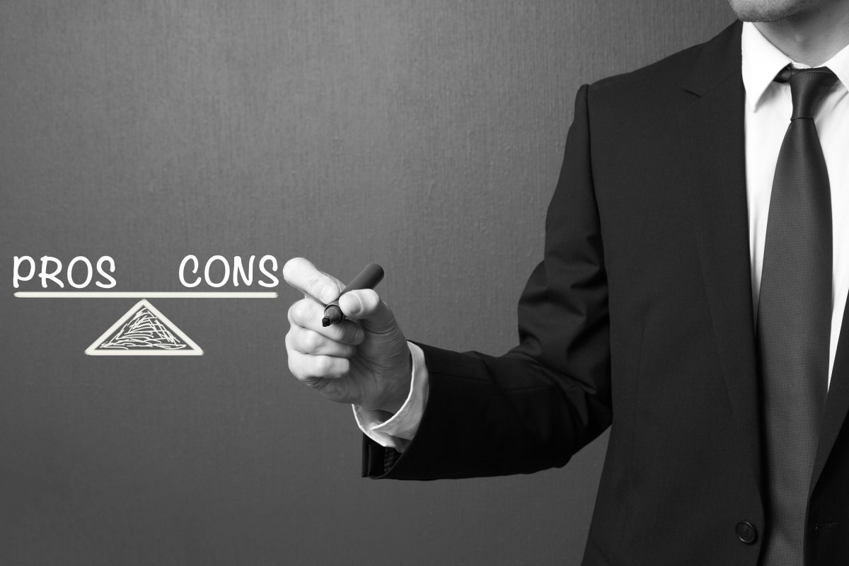Business man writing Pros and Cons - Balance Concept