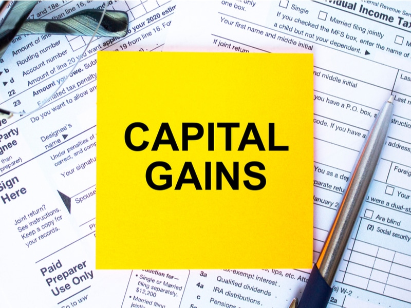 Capital gains written on sticky note on top of tax forms