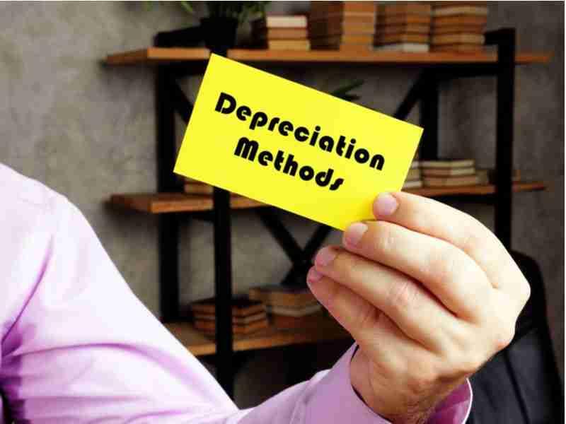 "Business man holding ""depreciation methods"" sign"