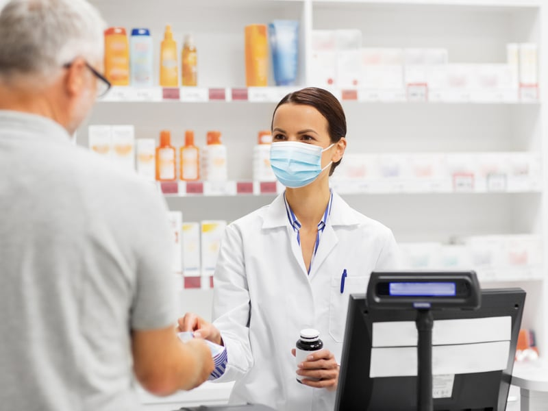 Female pharmacist handing a script over to a man