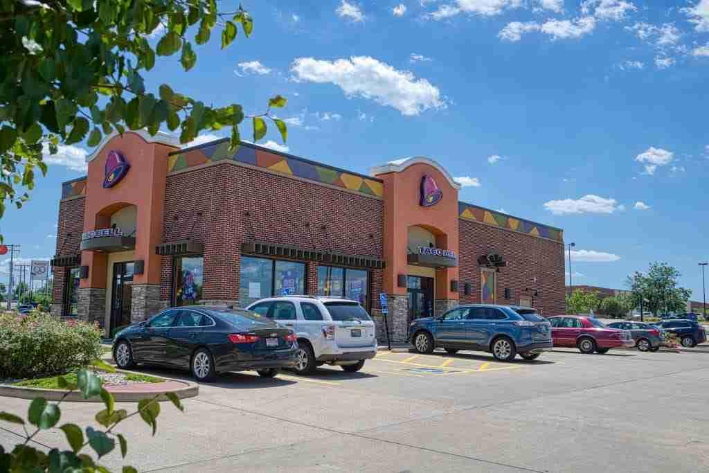 Taco Bell restaurant, blue sky, green trees