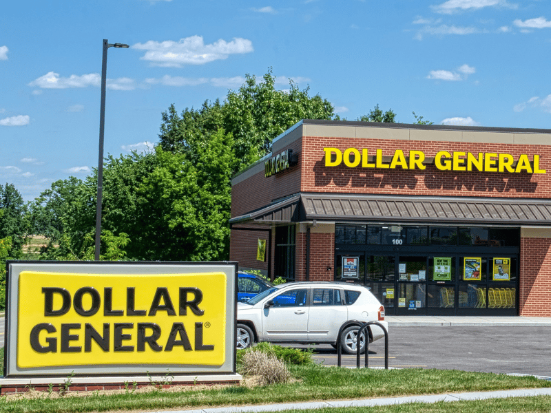Dollar General store with car in parking lot and yellow sign by the road